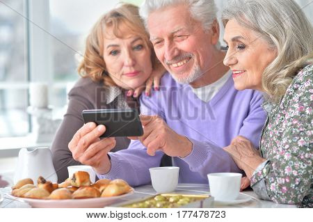 Portrait of elderly people having breakfast and using mobile phone