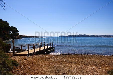 Playa desierta en primavera con su muelle para embarcaciones.