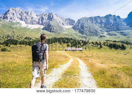 Young european man on walk through the mountains in summer, hiker walking in mountains, natural route for tourists in countryside