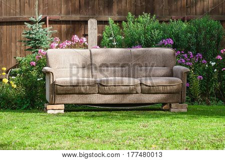 old sofa placed on bricks in green garden