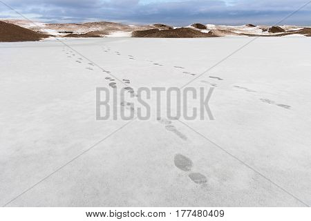 Two lines of footprints in the snow stretching into the distance. The landscape concept.