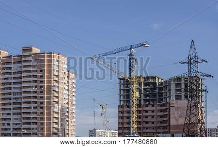 High-voltage masts against the background of high-rise buildings under construction