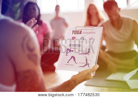 Close up of yoga position on clipboard with a class in the background