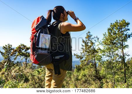 Hiker woman look binoculars on the mountain background blue sky Thailand