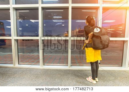 Traveler woman at the airport window,girl waiting for the arrival of the aircraft