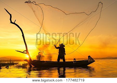 fisherman throwing net catching fish in the lake