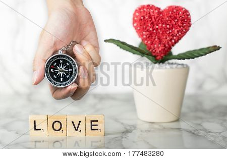 Holding Compass for direction for love with heart flower