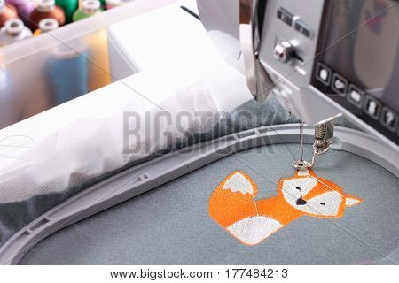 Embroidery with embroidery machine - fox theme - machine and background with box of bobbins blurry