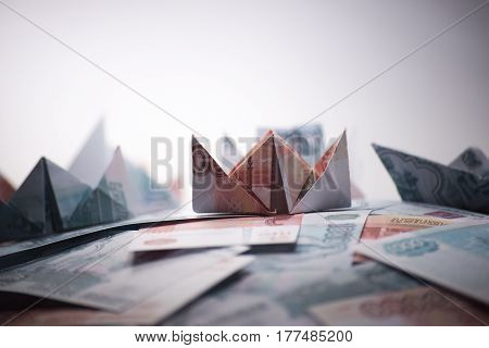 ship origami banknotes on a background of money