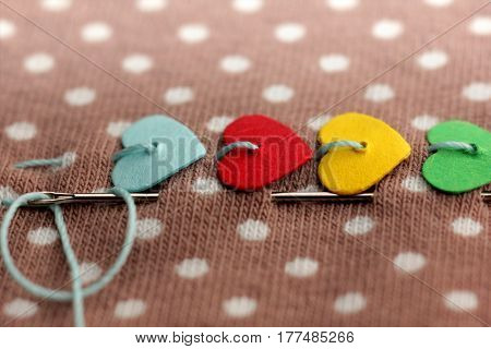 macro of colorful hearts stitched on dotted fabric with needle and thread