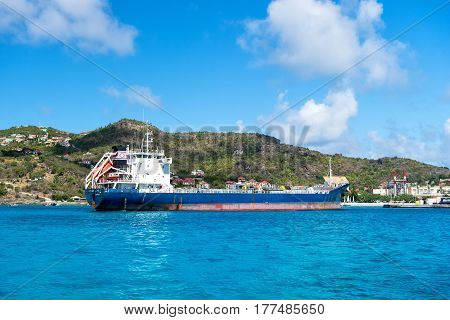 St. Barts - January 01 2016: big cargo ship or barge blue color in French island bay of Saint Barth
