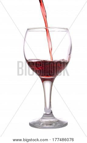 Stream of red wine flows in a wineglass isolated on white