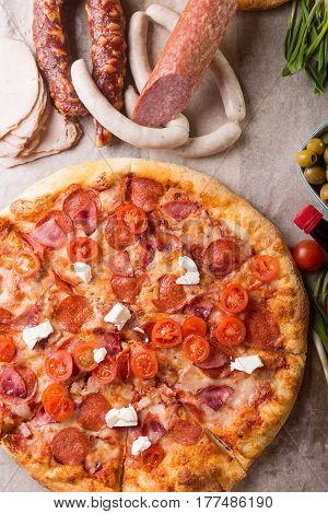 Rustic pizza with salami mozzarellabasil top view with copy space. Two pizzas on a wooden table. Pizza salami on wooden background. Pizza salami with tomatoes and olives.