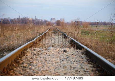 old track passing through the field to the factory