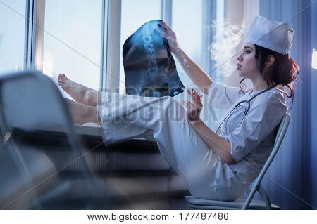 Brunette sassy female nurse in uniform smoking a cigarette and looking at x-ray picture of backbone