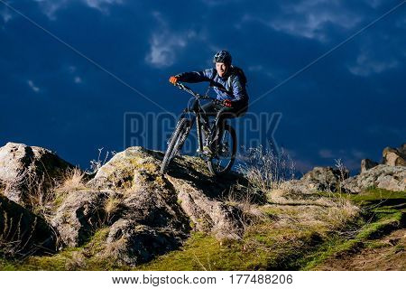 Enduro Cyclist Riding the Bike on the Rock at Night. Extreme Sport Concept. Free Space for Text.