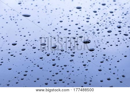 Blue surface with water drops. Focus on foreground abstract texture and background