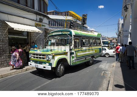Sucre Bolivia - December 5 2013: People and an old bus in a street in the city of Sucre in Bolivia.
