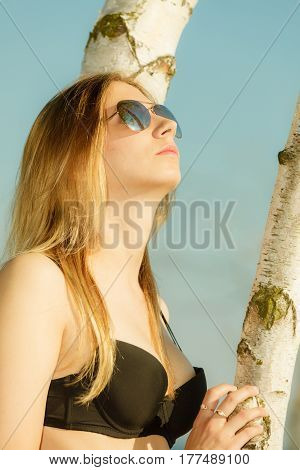 Summertime underwear summer clothes concept. Woman wearing black bikini posing next to tree relaxing on beach.
