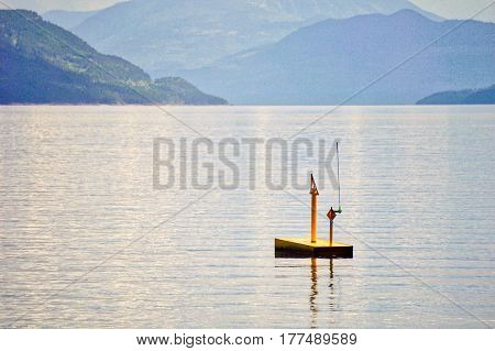 A yellow buoy on calm blue waters
