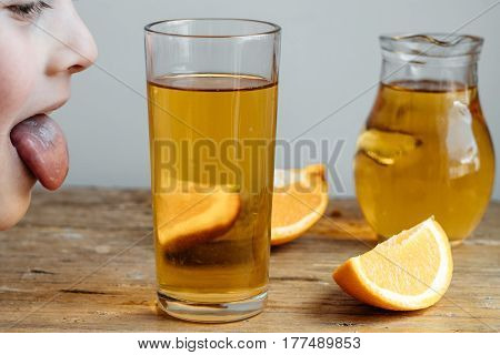 Cute Boy With Homemade Kombucha In A Decanter With Orange  On A Wooden Table.