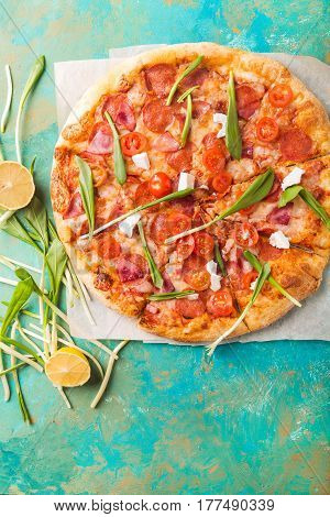 Spring pizza. Salami pizza. Pizza salami on a turquoise abstract background. Copyspace
