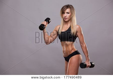 Beautiful athletic woman pumping muscles with dumbbells, isolated on grey background with copyspace.