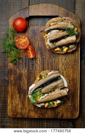 Appetizing sandwiches with sprats and egg on wooden background top view