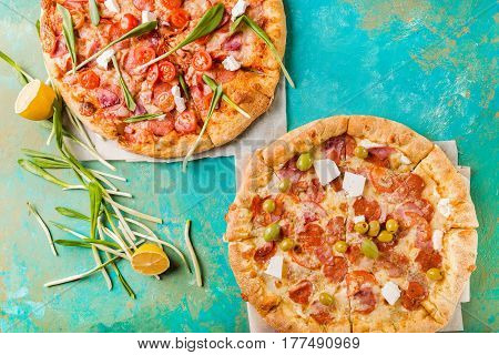 Spring pizza. Salami pizza. Pizza salami on a turquoise abstract background. Two pizzas. Copyspace