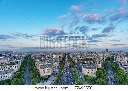 Wide angle skyline of Paris with Champs-Elysees, Montparnasse tower and Sacre Coeur at sunset