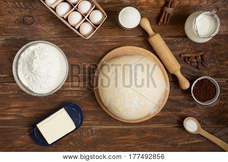 Ingredients for making cinnamon rolls on a wooden background . Flour , sugar, egg , chocolate , cocoa , cinnamon , butter and dough. Close up. Top view