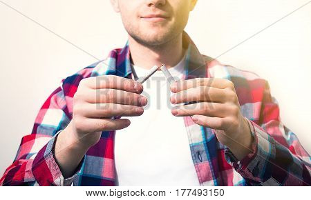 man guyhipster holding a broken cigarette concept of healthy lifestyle quit smoking on a white background in a white shirt
