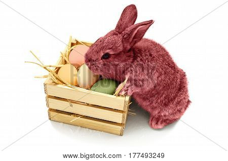 Cute little easter bunny with wooden box full of easter colored eggs isolated on white background. Pink rabbit.