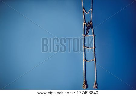 Wooden Dark Mannequin Standing On The Hanging Rope Ladder On The Bright Blue Background. Life Concep