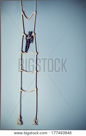 Wooden Dark Mannequin Standing On The Hanging Rope Ladder On The Blue Background. Life Concept. Sele