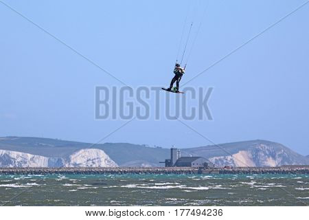 kitesurfer jumping on his board in Portland harbour