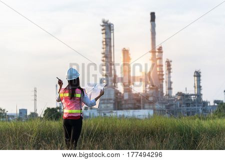 Double exposure of Engineer with safety helmet in front of Oil refinery and gas industry - refinery at sunset background Business Insustrail concept