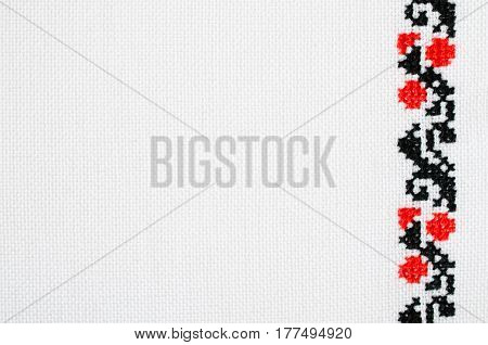 Texture of White Canvas With Slavic Red and Black Embroidery by Cross-stitch. Ukrainian Embroidery for Background.