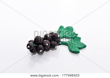 Black currant made from plasticine. Isolated on white background.
