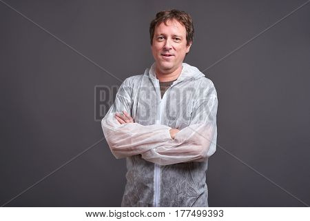 A happy middle aged man standing and smiling in a clothes protector suit
