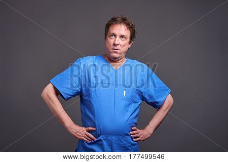 A middle aged male doctor standing in a blue scrub and feeling bored