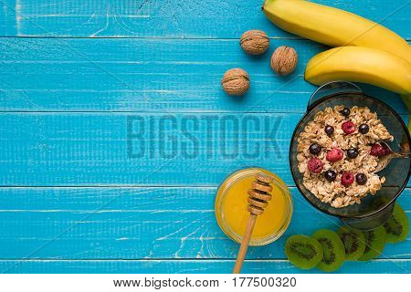 oatmeal porridge with banana, kiwi fruit, nuts and honey in a bowl with egg for healthy breakfast on rustic wooden background. Healthy food for Breakfast. Top view. Copy space