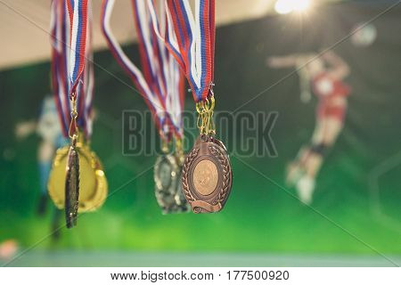 Gold silver bronze medals in volleyball against the background of a poster with volleyball players