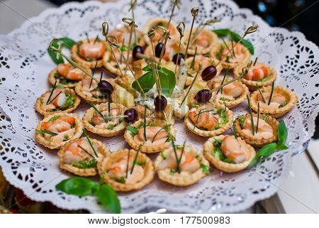 A dish with festive canapes, stands on a table