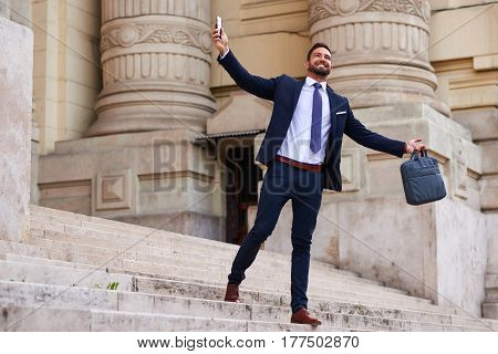 A handsome young businessman walking down on the stairs and celebrating