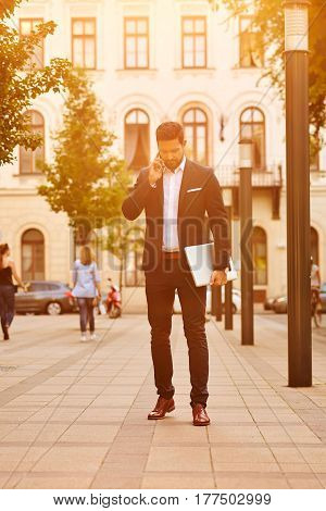A handsome young businessman holding his laptop while talking on his phone and walking on the sunny street