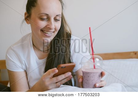 Young Woman Sitting On A Bed After Waking Up In The Morning, Smiling And Holding A Glass Of Raspberr