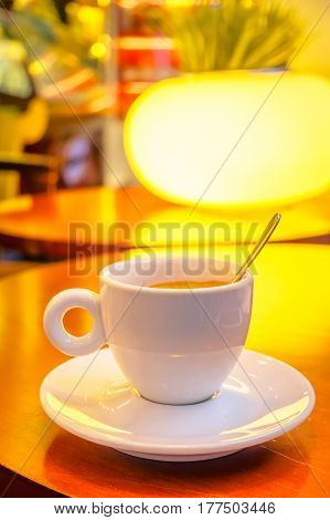 SHANGHAI, CHINA: Small white espresso cup sitting on saucer with coffee inside, cafeteria environment.