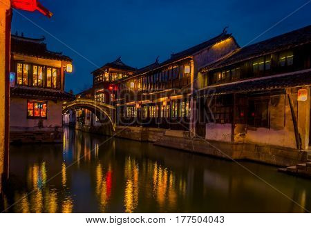 SHANGHAI, CHINA: Beautiful evening light creates magic mood inside Zhouzhuang water town, ancient city district with channels and old buildings, charming popular tourist area.