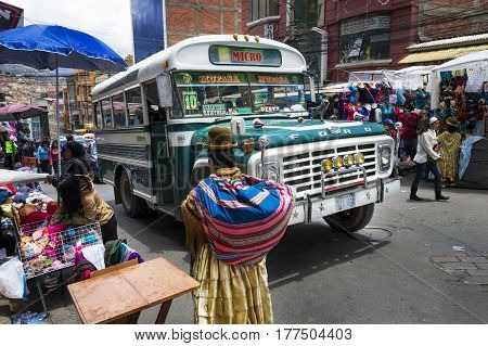 La Paz Bolivia - December 8 2013: Busy street scene with a bus and people in the city of La Paz in Bolivia.